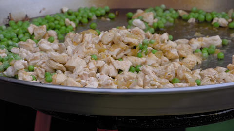 Slow motion: chef cooking chicken meat pieces, peas in huge wok - close up view Live Action