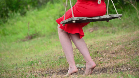 Woman in red dress swaying on swing, in green summer park. Pretty girl in red Live Action