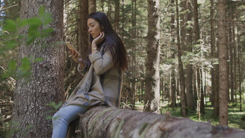 Pretty woman using smartphone in forest outdoors Live Action
