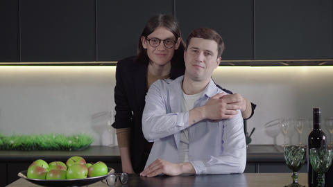 Portrait of adult Caucasian gay couple looking at camera and smiling. Camera Live Action