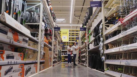 young men choose tools on shelves at modern hardware market Live Action