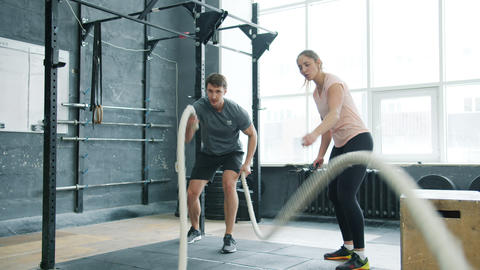 Active guy student doing ropes battling crossfit exercise training with female Live Action