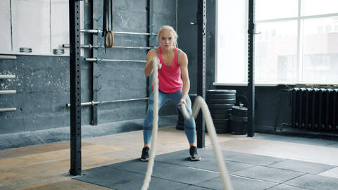 Portrait of young woman working out with rope during crossfit training indoors Live Action