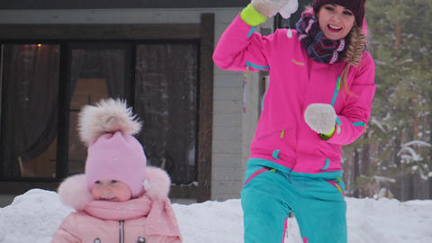 young woman throws snowball and little girl kid smiles Live Action