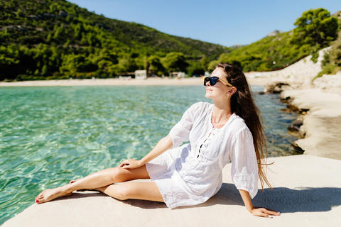 young woman relaxing on beach in summer dress Photo