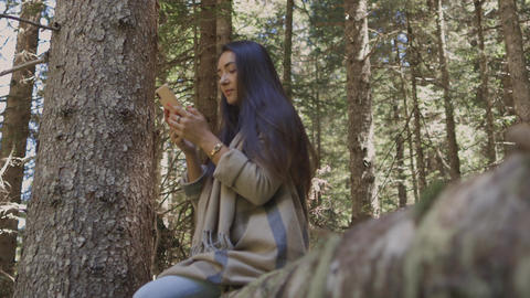 Attractive woman browsing smartphone in forest outdoors Live Action