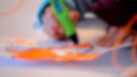 Blurred background. Face painting pictures 3d pen. The child draws Live Action