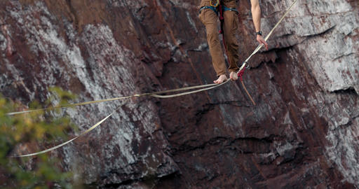 Dangerous extreme sport, a man is walking on the slackline over the quarry, 4k Live Action