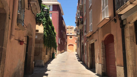 Tarragona, Spain, A narrow city street with buildings on the side of a building Live Action