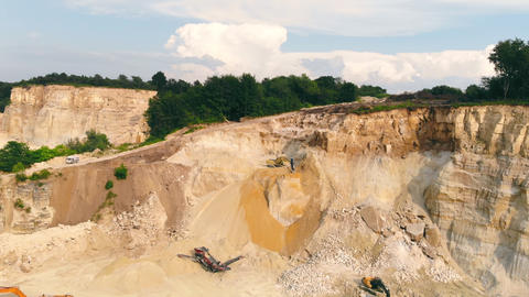 Excavator working in a sand quarry and extracting sand. An excavator picks up Live Action