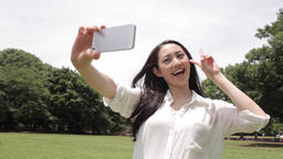 Attractive young Japanese woman taking selfie in a city park GIF 動畫