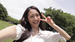 POV shot of attractive young Japanese woman taking selfie in a city park ภาพวิดีโอ