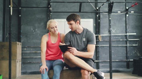 Joyful girl and guy talking relaxing after training in crosfit gym, trainer is Live Action