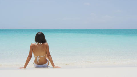 Beach vacation people - woman relaxing looking at perfect turquoise ocean water Live Action