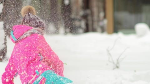 delighted lady in pink blue winter tracksuit lies on snow Live Action