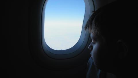 delighted boy admires landscapes outside airplane window Acción en vivo