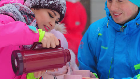 young woman pours hot tea into cup in husband hands in park Acción en vivo