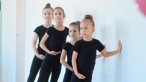 young girls lean on white wall and practice ballet moves Acción en vivo