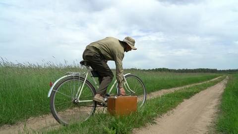 man on bicyle grabbing suitcase with treasures that he found on the country road Live Action