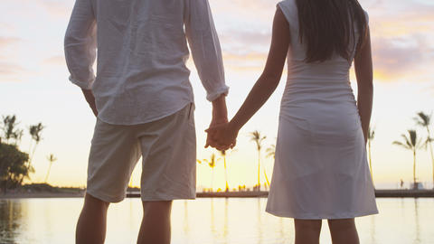 Honeymoon couple romantic at sunset holding hands in love enjoying vacation Live Action