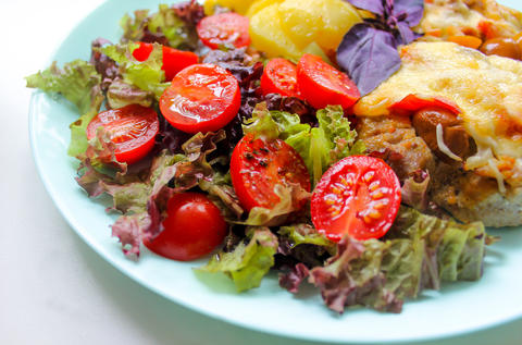 Prepared meat dish with potato slices and cherry tomatoes with salad Photo