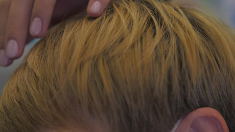woman hand straightens and finishes trendy short hairstyle Live Action