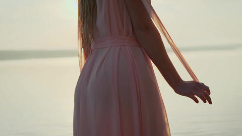 Young girl in white dress walking alone on the sandy tropical beach at sunrise Live Action