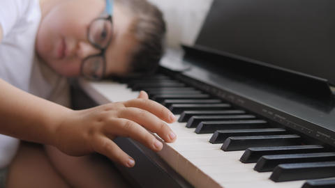 Electronic piano. Fingers press the piano keys. Music lesson. Child was tired in Live Action
