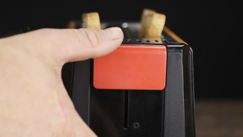 Close-up, hand includes a toaster with two slices of bread. Slow motion Live Action