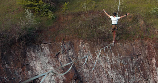 Danger, extreme sports, a man is walking on the tightrope over a massive pit, 4k Live Action