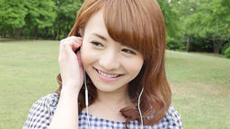 Young attractive Japanese woman listening to music in a city park Footage