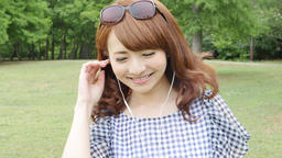 Young attractive Japanese woman listening to music in a city park 圖片