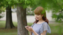 Young attractive Japanese woman with smartphone in a city park GIF 動畫