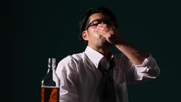 Depressed Japanese businessman taking pills with whiskey Footage