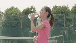 Young Japanese female tennis player drinking water on the court Footage