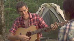 Slow motion footage of friends relaxing with guitar and drinks at a camp site, Y GIF