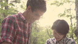 Slow motion footage of friends checking map at a camp site, Yamanashi Prefecture Footage