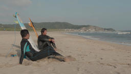 Japanese surfers talking sitting on the beach Footage