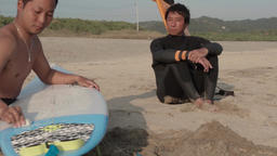 Japanese surfers talking sitting on the beach GIF