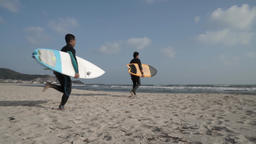 Japanese surfers going to the ocean with their boards Footage