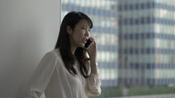 Attractive Japanese young woman talking on the phone in a modern office Footage