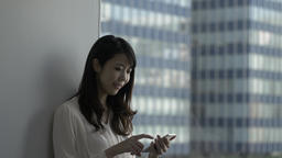 Attractive Japanese young woman with smartphone in a modern office GIF 動畫