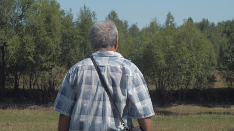 active pensioner in jeans walks along green lawn actively Live Action