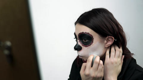 Girl paints her face white a traditional makeup for holiday of Santa Muerte Live Action