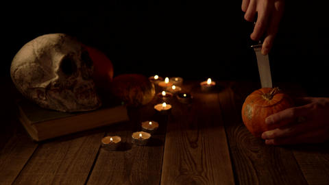 Carving the top of a pumpkin against the background of a skull and candlelight Live Action