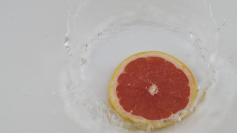 Fall of red slice of grapefruit, pomelo in white water. Slow motion Live Action