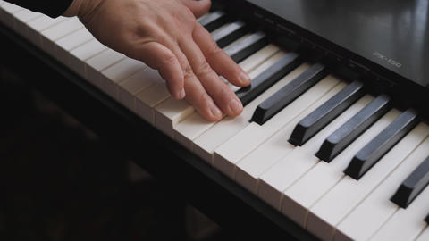 Electronic piano. Fingers press the piano keys. Music lesson Live Action