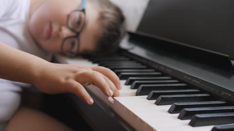 Electronic piano. Fingers press the piano keys. Music lesson. Child was tired in the lesson and lay Live Action