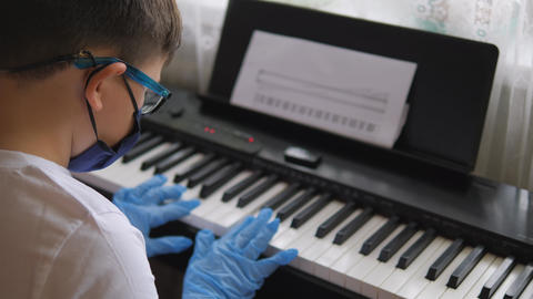 Electronic piano. Fingers press the piano keys. Hands in rubber gloves. Pandemic Live Action