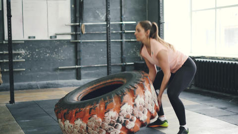 Young fit sportswoman lifting heavy rubber tyre during sports workout indoors Live Action